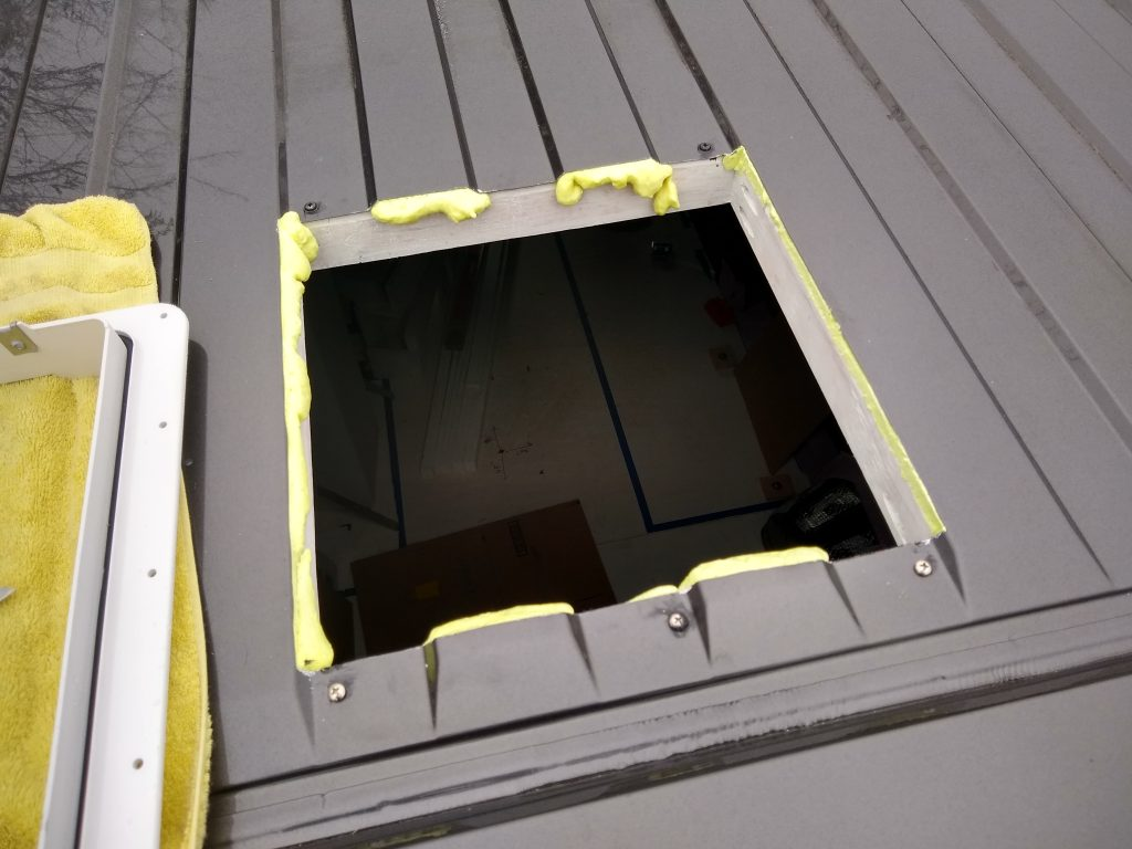RV roof vent fan opening with a wooden frame and expanding foam.