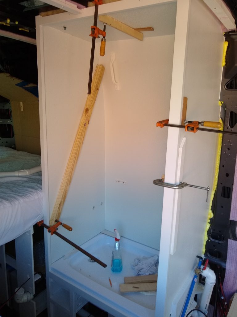 Clamping the white panels to the wet bath shower walls.